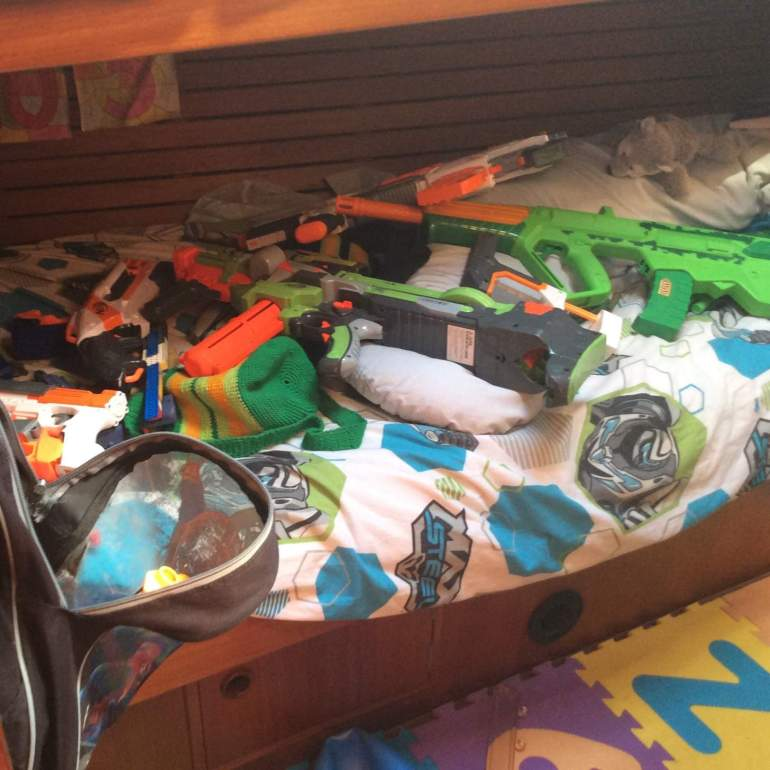 The boys room - bed covered in toy guns