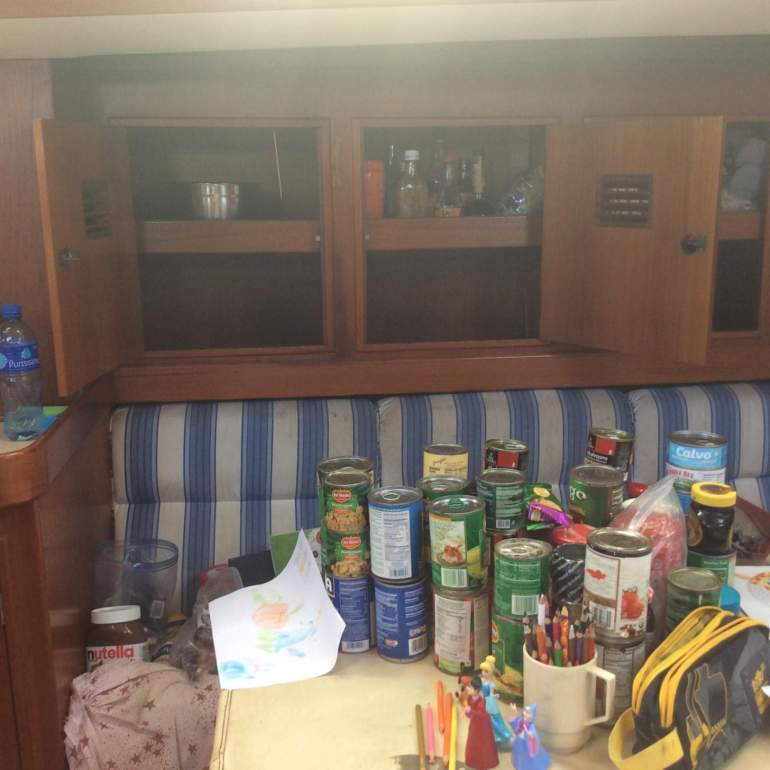 Cans on the table and an empty cupboard